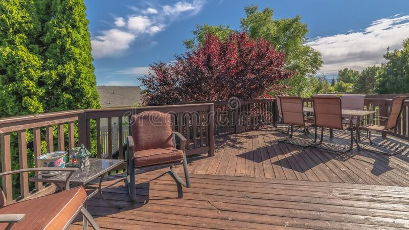 Pano Furniture on the balcony of home with brown wooden floor railing and stairs. The outdoor living space has a scenic view of the yard, trees, and blue sky stock photo