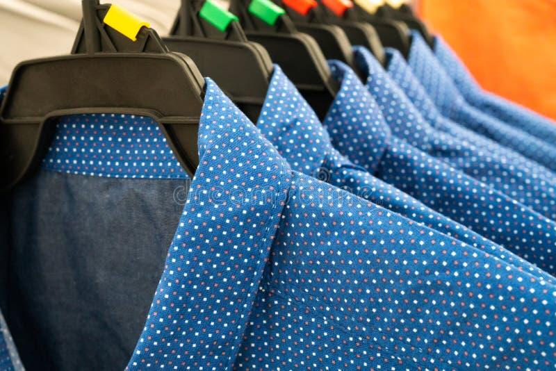 Pano masculino, fileira de camisas azuis do homem no gancho no armário fotos de stock royalty free