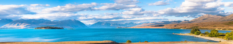 Panolama view of Beautiful scene of blue lake, yellow grassland, mt cook and blue blue sky with cloud beside lake Tekapo before. Sunset stock image