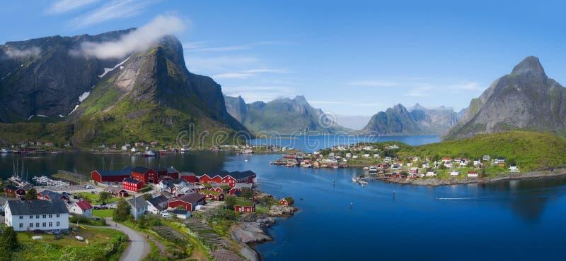 Panorama aéreo bonito do mar azul que cerca a aldeia piscatória e os picos rochosos Reine, Moskenes, Lofoten, Noruega, ensolarada imagens de stock