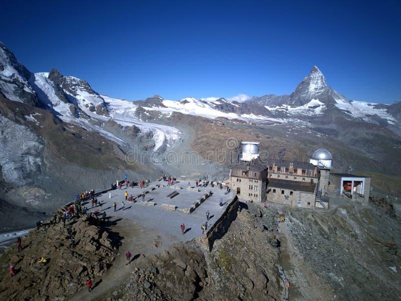 Panorama aérien de montagne majestueuse Matterhorn à la lumière du soleil de matin avec l'observatoire célèbre de Gornergrat photos stock