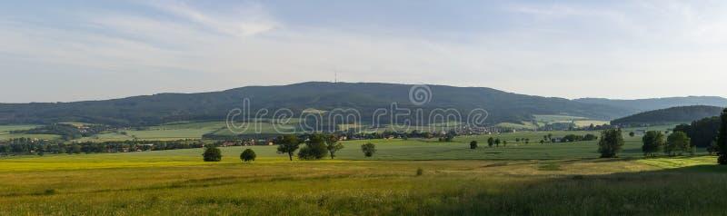 Panorama aan landelijk Tsjechisch landschap met tarwegebied, heuvel Klet en bomen bij zonsondergang royalty-vrije stock foto