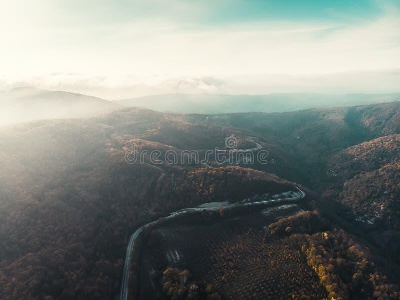 Panorama aereo del paesaggio del sole e della foschia di mattina sopra le belle montagne con la strada della curva fotografia stock libera da diritti