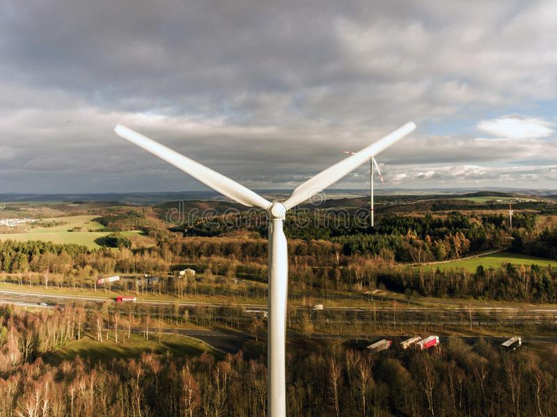 Panorama aerial helicopter view over wind farm landscape in Germany with white generator turbines. A panorama aerial helicopter view over wind farm landscape in royalty free stock images