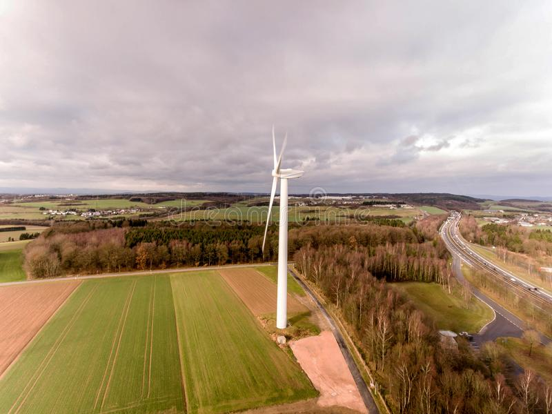 Panorama aerial helicopter view over wind farm landscape in Germany with white generator turbines. A panorama aerial helicopter view over wind farm landscape in royalty free stock photos