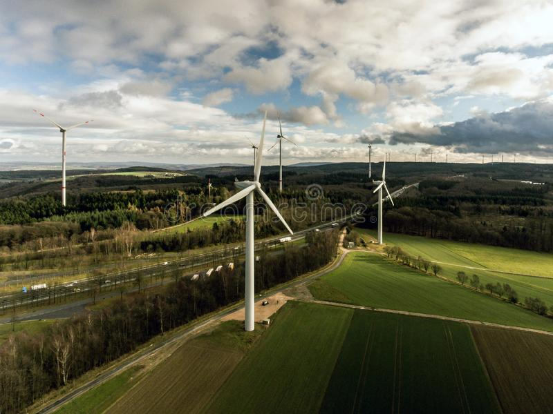 Panorama aerial helicopter view over wind farm landscape in Germany with white generator turbines stock photos