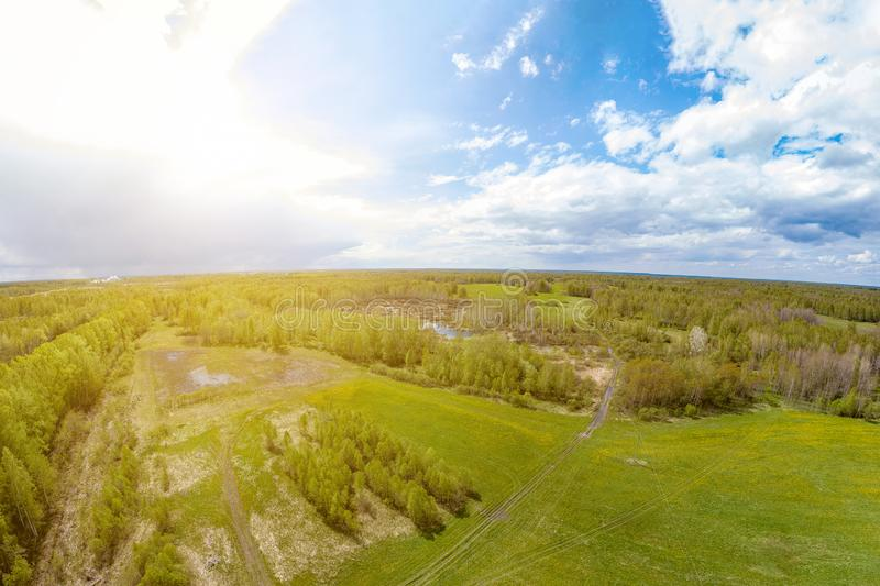 Panorama aerial view of green meadow and field near the path around which are gray and white clouds with a blue sky with a country stock images