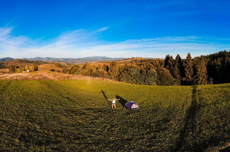 Panorama aerial view of happy hiker woman with open arms stay near tent around mountains sunset horizon enjoying the leisure stock photos