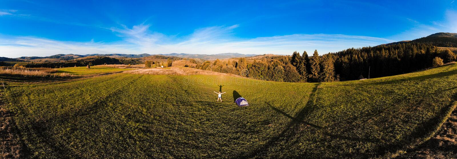 Panorama aerial view of happy hiker woman with open arms stay near tent around mountains sunset horizon enjoying the leisure royalty free stock images