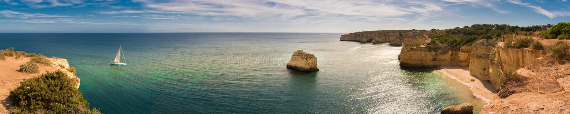 Panorama Algarve linia brzegowa w Portugalia z żeglowanie łodzi chodzeniem w kierunku Marinha plaży zdjęcia stock