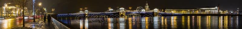 Panorama amplio de la noche en el puente, Neva River y edificios abiertos illumunated del palacio en el terraplén fotos de archivo