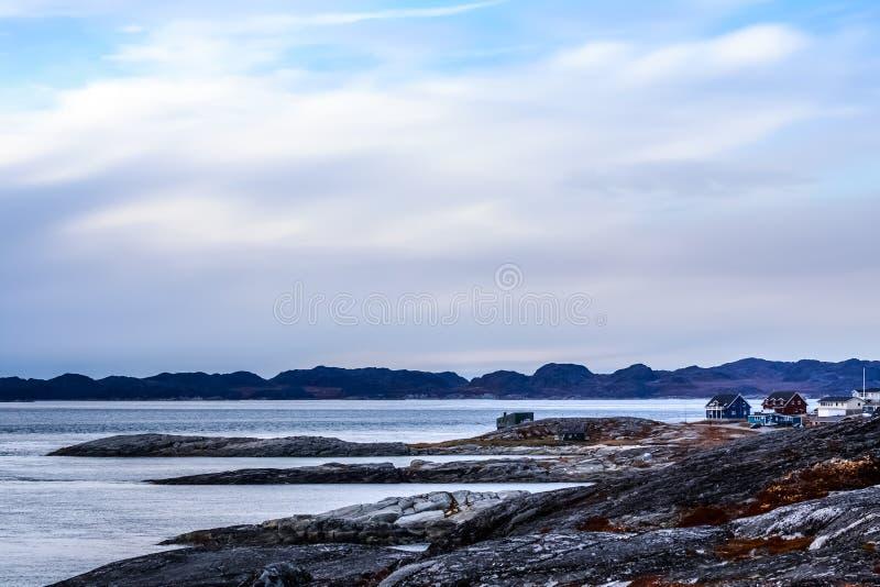 Panorama arctique de fjord avec des maisons au rivage pierreux de toundra à a photographie stock libre de droits