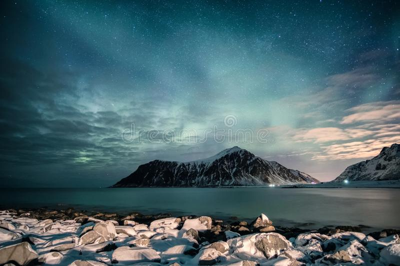 Aurora borealis with stars over mountain range with snowy coastline at Skagsanden beach stock photo