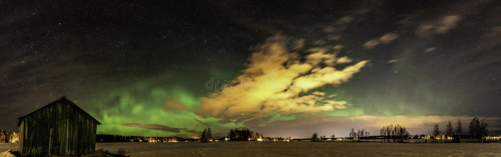Panorama of Aurora and stars shine over abandoned shed standing alone in the field, deep autumn, winter and clear skies with come stock photo