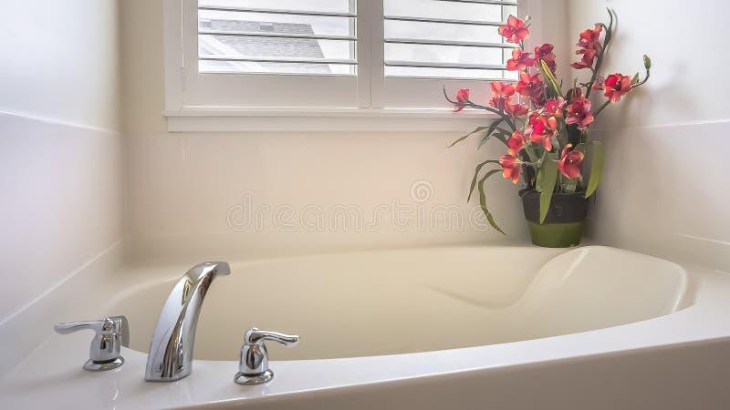 Panorama-Ausgangsbadezimmer mit einer Badewanne installiert vor dem Fenster mit Vorhängen lizenzfreie stockbilder