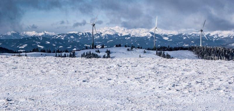 Panorama austríaco dos cumes do inverno com turbinas eólicas e picos cobertos de neve foto de stock
