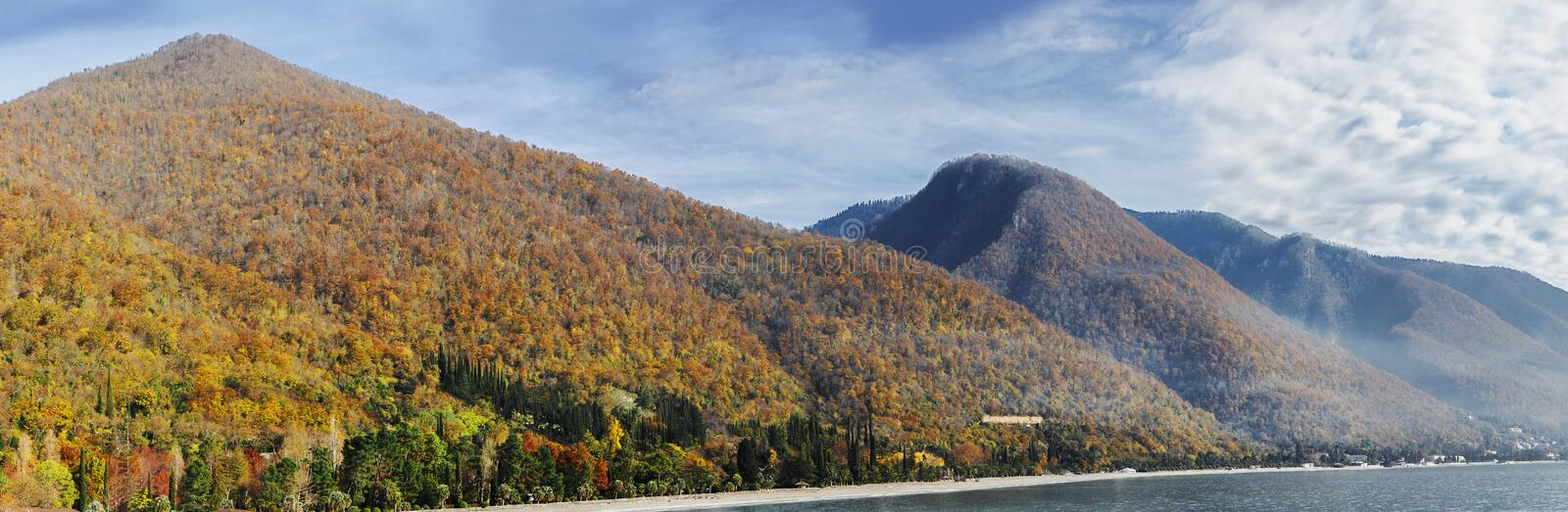 Panorama of the autumn haze-covered hills and a cloudy blue sky. Hilly colored forests natural autumn landscape in orange, red aut stock image