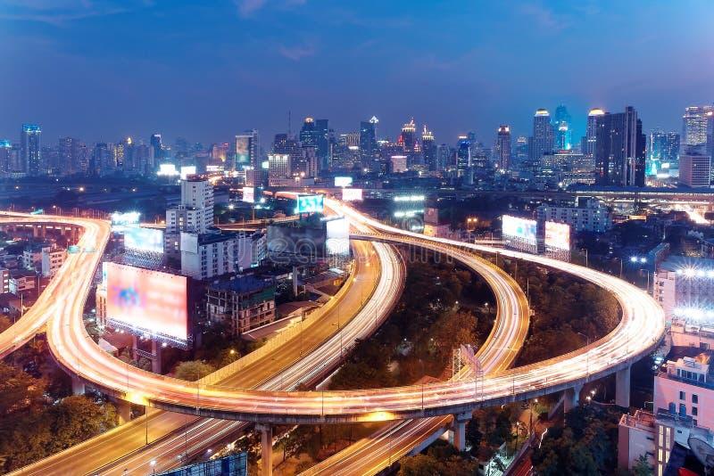 Panorama av Bangkok på skymning med skyskrapor i bakgrund och trafik skuggar på högstämda motorvägar & cirkulärutbyten arkivbilder