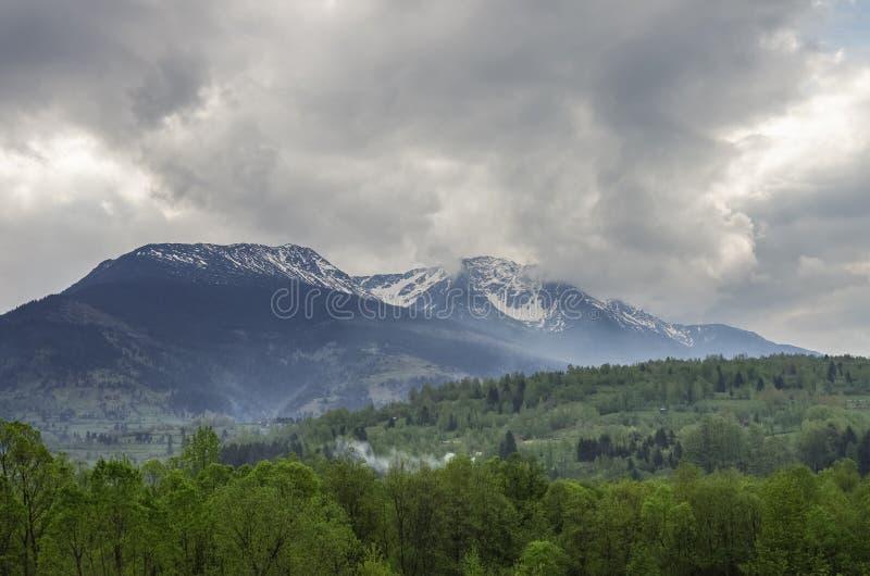 Panorama av Carpathians berg med stormig molnhimmel och sno royaltyfri foto
