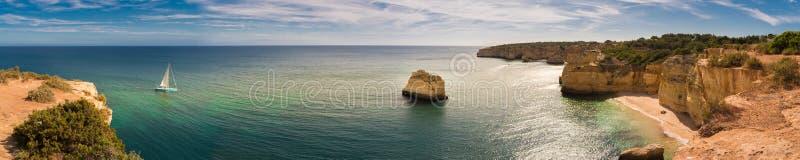 Panorama av den Algarve kustlinjen i Portugal med en segelbåtflyttning in mot den Marinha stranden arkivfoton
