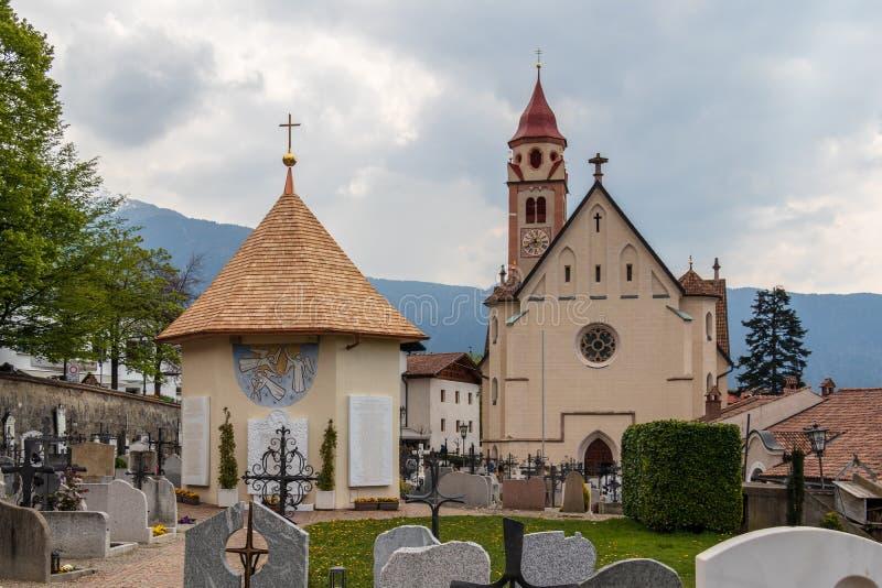 Panorama av den huvudsakliga kyrkan, der Taufer för Pfarrkirche St Johannes, med kyrkogården och kapellet i kommunbyn av Tirol arkivbild