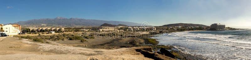Panorama av den Playa del Cabezo stranden med närliggande ferie- och semesterhus, El Medano, Tenerife, Spanien royaltyfri bild