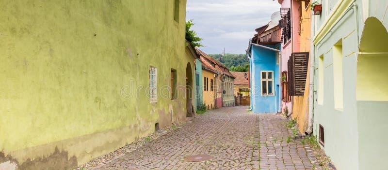 Panorama av en färgrik cobblestoned gata i Sighisoara royaltyfri foto