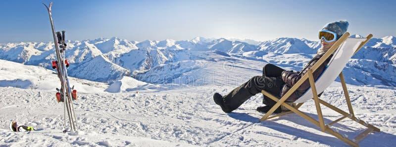 Panorama av en flicka som solbadar i en deckchair nära ett snöig, skidar lutningen royaltyfria bilder