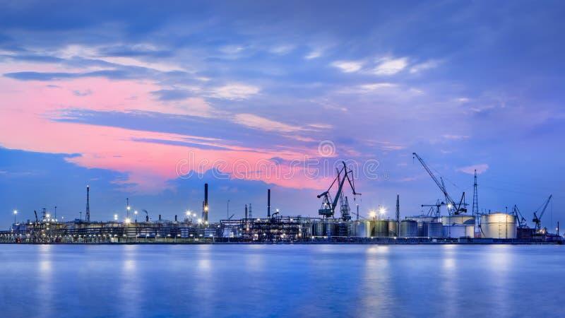 Panorama av en petrokemisk fabrik mot en dramatisk kulör himmel på skymning, port av Antwerp, Belgien arkivfoton