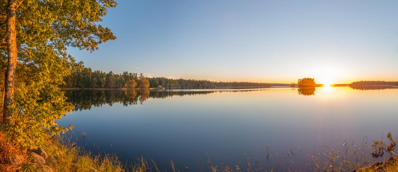Panorama av en solnedgång på en sjö arkivfoton
