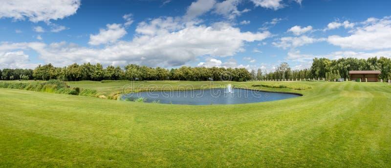 Panorama av golfbanan med dammet i solig dag royaltyfri foto