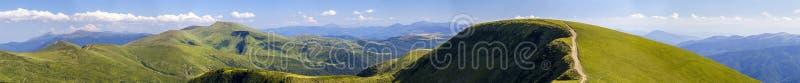 Panorama av gröna kullar i sommarberg med grusvägen för arkivfoto
