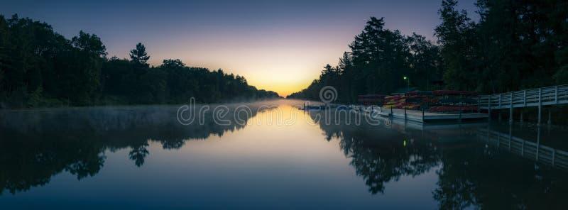Panorama av mjuk mist över floden i predawnsoluppgångljus arkivfoto