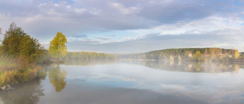 Panorama av morgonhöstlandskapet på sjön med dimma, björkskog på kusten, Ryssland, Ural royaltyfri bild