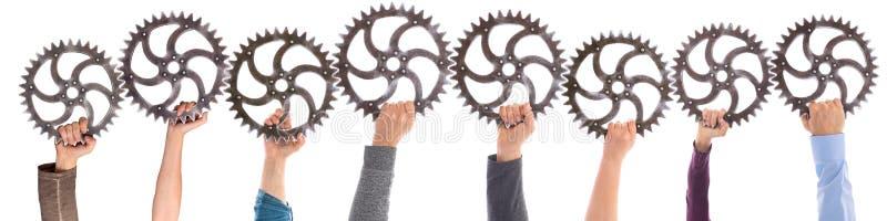 Panorama av olika händer som rymmer att koppla ihop för kugghjul arkivfoton