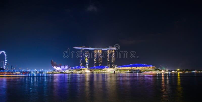 Panorama av Singapore stadshorisont med det Marina Bay Sands hotellet och det ArtScience museet på natten royaltyfri foto