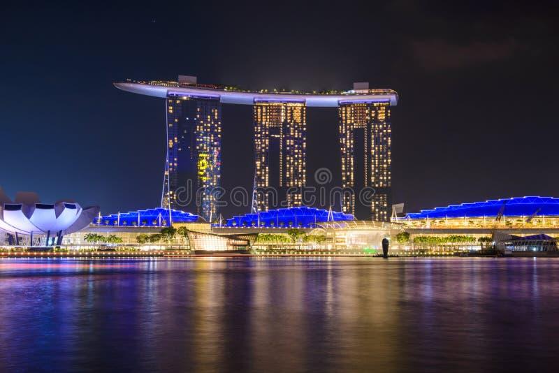 Panorama av Singapore stadshorisont med det Marina Bay Sands hotellet och det ArtScience museet på natten fotografering för bildbyråer