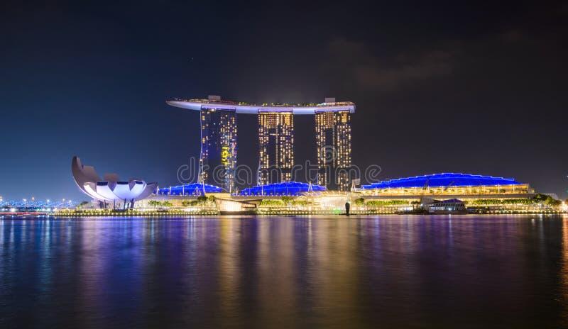 Panorama av Singapore stadshorisont med det Marina Bay Sands hotellet och det ArtScience museet på natten arkivfoton