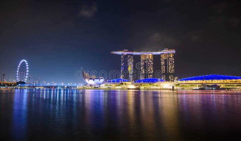Panorama av Singapore stadshorisont med det Marina Bay Sands hotellet och det ArtScience museet på natten royaltyfri bild