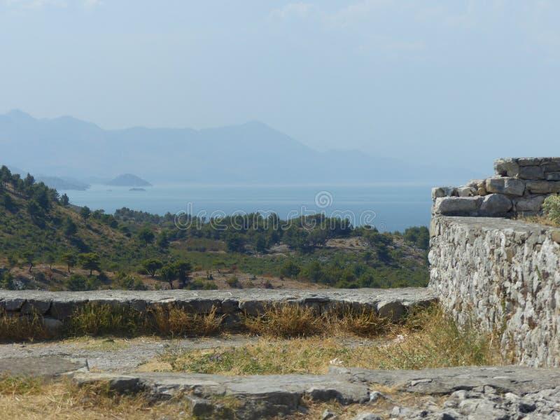 Panorama av sjön av Skadar med bergen trots allt med thdetaljen av en forntida vägg av en fasthet i nord av Albanien arkivfoton