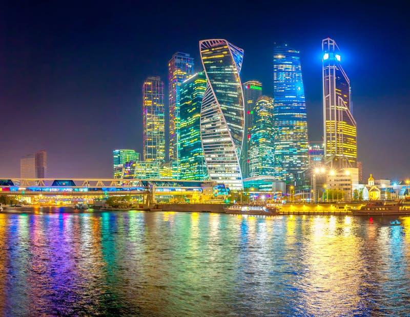 Panorama av skyskrapor av Moskvastaden med reflexioner i Moskvafloden på natten royaltyfri foto