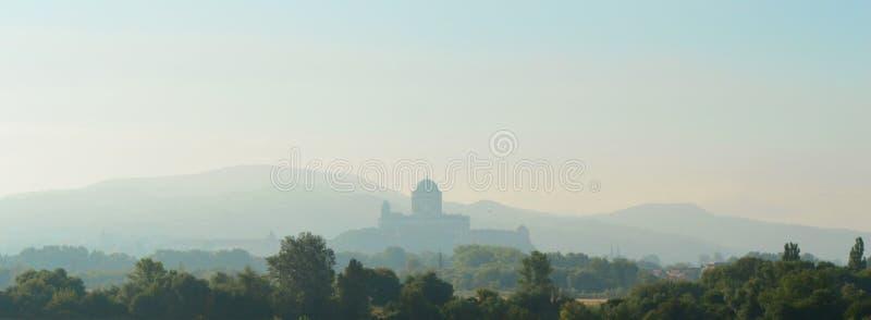 Panorama av soluppgång över kyrkan och kullarna royaltyfri foto