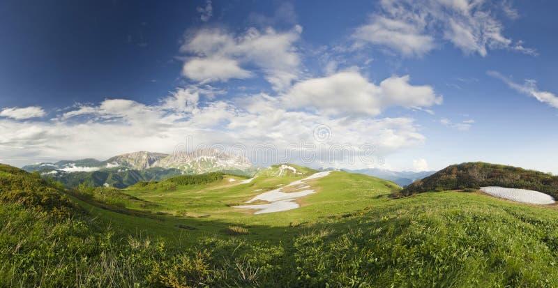 Panorama av sommarsnöberg med den stora gräsdalen royaltyfri foto