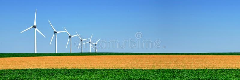 Panorama av vindturbiner arrangera i rak linje i ett fält royaltyfri fotografi