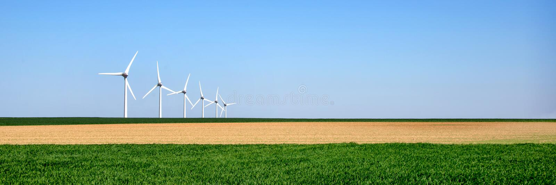 Panorama av vindturbiner arrangera i rak linje i ett fält royaltyfri bild