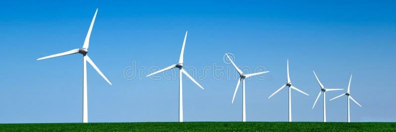 Panorama av vindturbiner arrangera i rak linje i ett fält fotografering för bildbyråer