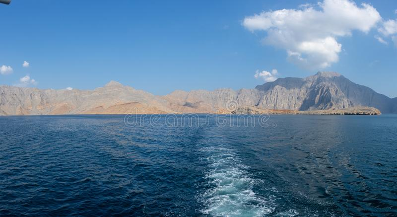 Panorama from the back of a Dhow Boat looking to the Fjords, beautiful blue water, mountains and clouds of Musandam, Oman in the. Middle East royalty free stock photos