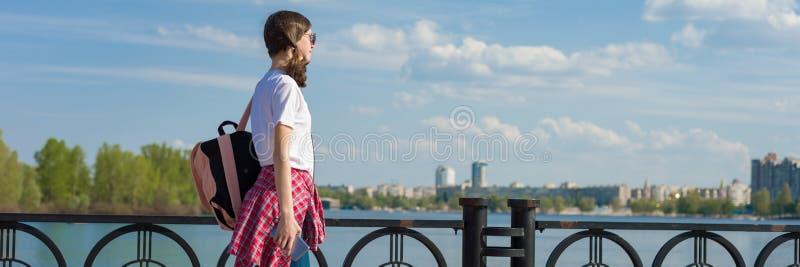 Panorama- baner av den kvinnliga studenten som går utomhus- Tonårig flicka i den vita t-skjortan med ryggsäcken, bakgrundshimmel  royaltyfri bild