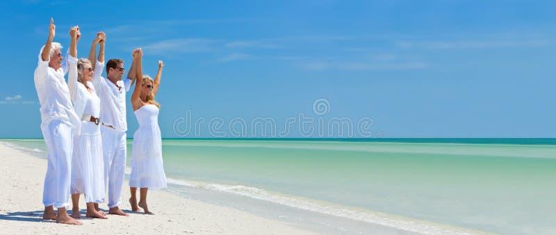 Panorama- banerfamilj som firar på den tropiska stranden arkivbild