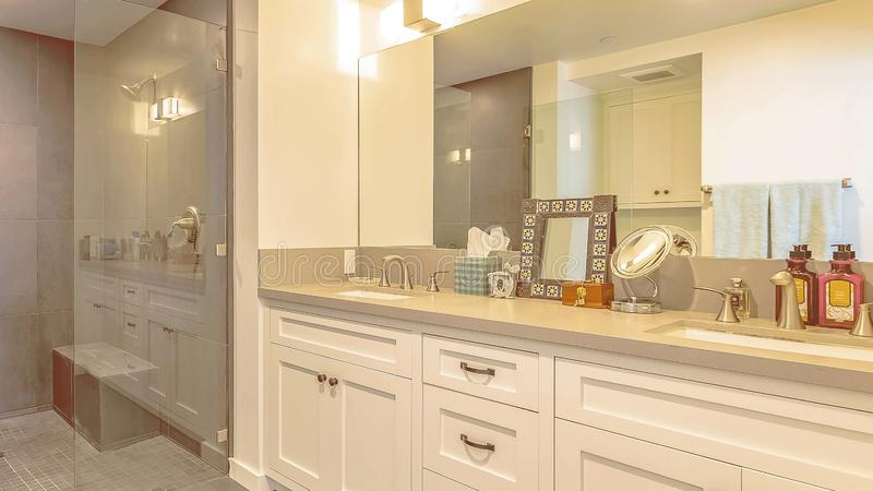 Panorama Bathroom interior with shower separated from the vanity area by a glass door. The vanity has wood cabinets, double sink, and large mirror royalty free stock image
